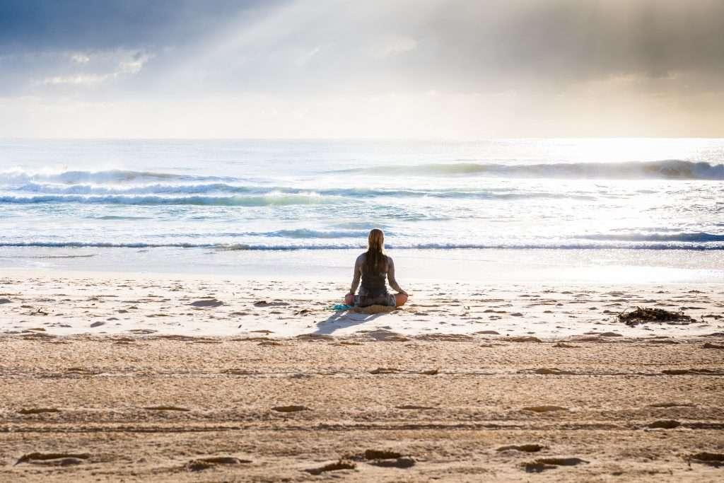 Mulher meditando de frente para o mar. Comece a meditar